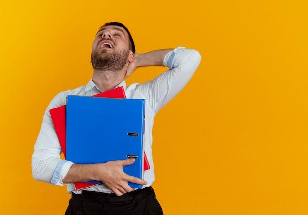 不機嫌なハンサムな男は、オレンジ色の壁に分離されたファイルフォルダーを保持する後ろに頭に手を置きます