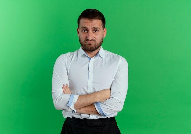 L'uomo bello scontento sta con le braccia incrociate isolate sulla parete verde