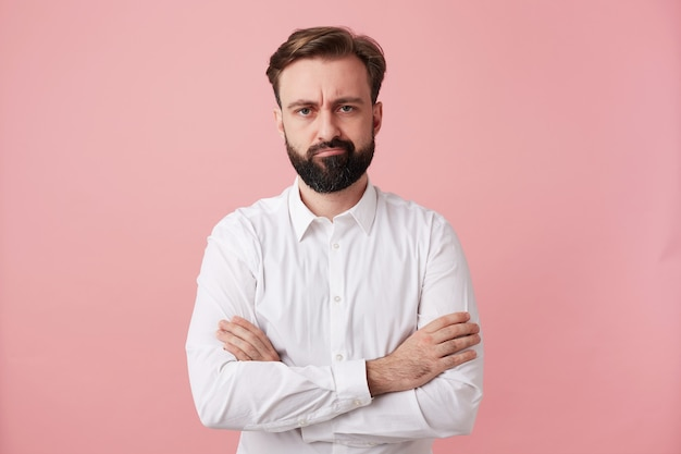 Displeased handsome young brunette male with beard keeping hands folded while standing against pink wall, frowning face and twisting his mouth, dressed in formal clothes