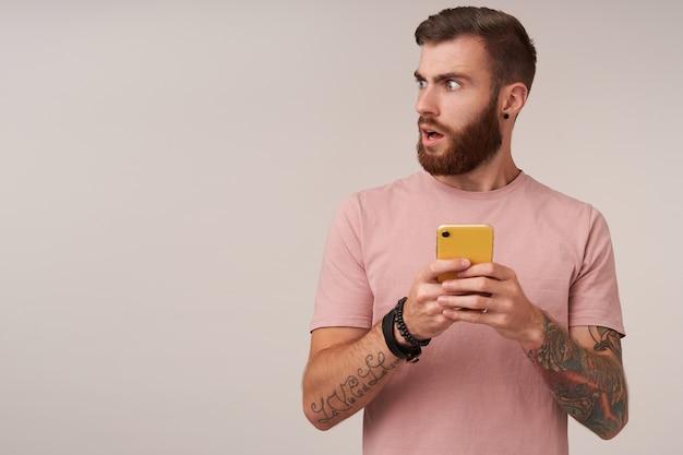 Uomo brunetta tatuato bello giovane scontento con la barba che osserva da parte con il broncio, mantenendo il telefono cellulare in mani alzate mentre si sta in piedi su bianco