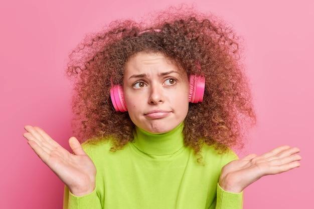 Недовольная нерешительная кудрявая европейка раскидывает ладони с невежественным выражением лица, не может принять решение, слушает музыку через беспроводные наушники, небрежно одетая, изолирована на розовой стене