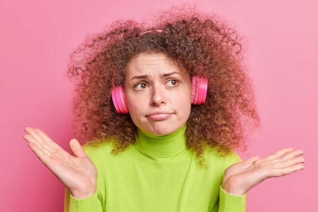 Displeased hesitant curly haired european woman spreads palms has clueless expression cannot make decision listens music via wireless headphones dressed casually isolated over pink wall