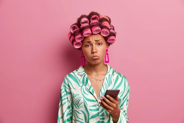 Il fidanzato triste della casalinga scontenta non chiama, tiene in mano il cellulare e aspetta un messaggio desiderabile, sconvolto a causa della data posticipata, indossa bigodini e abito di seta, sembra infelice