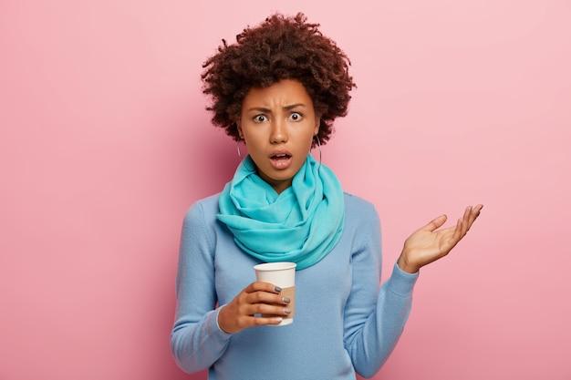 곱슬 헤어 스타일을 가진 불쾌한 분개 어두운 피부의 여인이 손을 들고 좌절감을 느끼며 캐주얼 파란색 옷을 입고 분홍색 벽 위에 고립 된 테이크 아웃 커피를 보유하고 있습니다. 부정적인 감정
