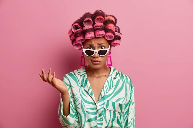 Недовольная возмущенная женщина носит бигуди для укладки волос, поднимает руку и недоумевает от неприятных новостей, носит стильные солнцезащитные очки и халат, стоит в помещении у розовой стены.