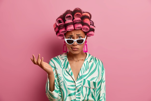 Displeased indignant woman wears curlers for getting hair styled, raises hand and puzzled by unpleasant news, wears stylish sunglasses and dressing gown, stands indoor against pink wall