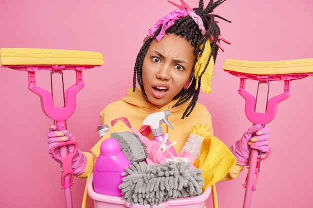 Displeased indignant young afro american woman with combed braids holds two mops