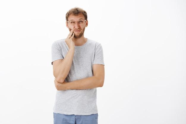 Раздосадованный очаровательный европейский мужчина со щетиной щурится и морщит нос, касается щеки, чувствуя болезненную зубную боль, кариес или проблемы с зубами