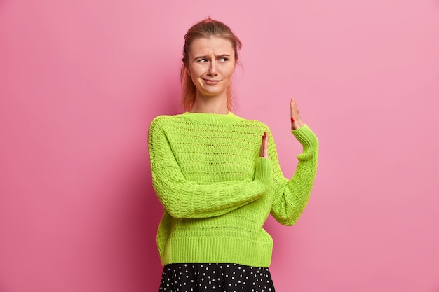 Displeased intensed woman shows refusal gesture, pulls palms in rejection sign, frowns from dislike, dressed in casual oversized jumper