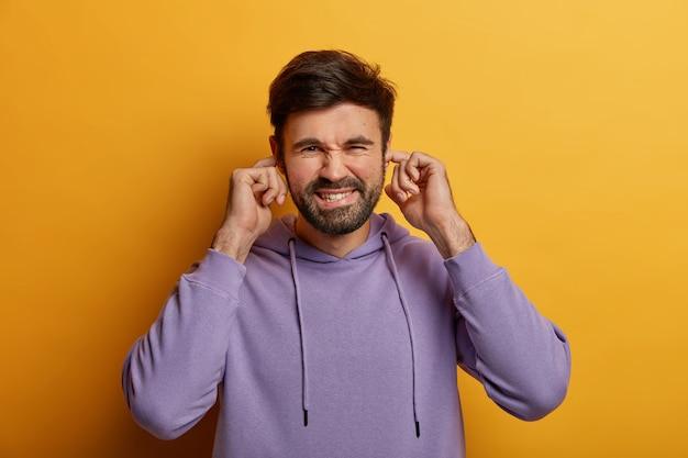 Displeased irritated man plugs ears, cant stand loud noise or sound, ignores conflict, wears violet hoodie, isolated on yellow wall. body language concept. youngster doesnt want to hear music