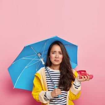 불쾌한 한국 여성이 손수건을 들고 추운 비오는 날씨에 감기에 걸리고 코를 흘리고 우산 아래에 숨어 있습니다.