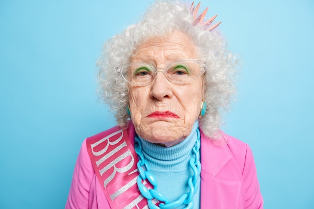 Displeased lonely retired old woman has wrinkled well cared face looks disappointed and gloomy celebrates birthday alone dressed in stylish clothes