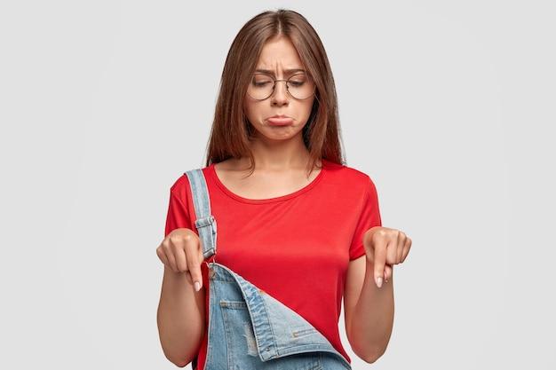 動揺した表情で不機嫌な素敵なブルネットの若い女性は、下向きに、不快な何かに気づき、動揺した表情をして、赤いtシャツでファッショナブルなオーバーオールを着て、白い壁にポーズをとる