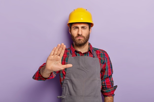 Displeased male engineer makes rejection gesture, says no, keeps palm outstretched at camera