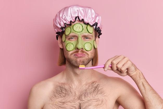 Недовольный мужчина наносит на лицо зеленую питательную маску с кусочками огурца для омоложения кожи, грустно смотрит в камеру, чистит зубы, стоит топлес в помещении на розовом фоне.