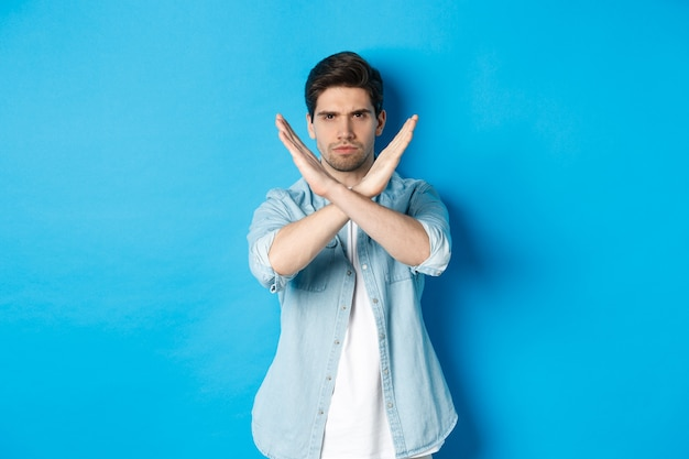 Displeased man frowning and saying no, making cross sign, tell to stop, standing against blue background