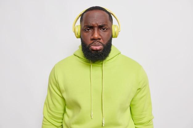 不機嫌そうな男は、白い壁に隔離された快適な緑のスウェットシャツを着て、ワイヤレスヘッドフォンを介してオーディオトラックを聞いて不機嫌そうな表情をしています