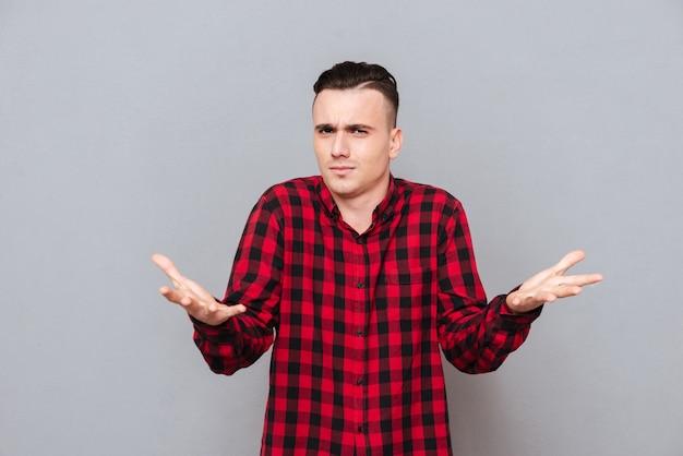 Недовольный мужчина в рубашке делает недовольный жест