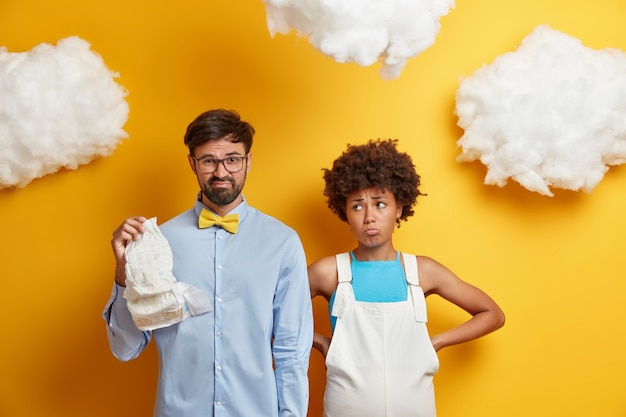 Displeased man looks with aversion at diaper being not ready to become father dressed in formal shirt. unhappy pregant woman prepares for child birth stands near husband against yellow wall