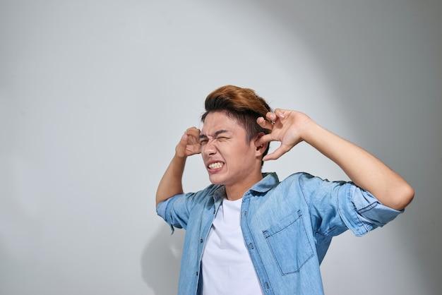 손가락으로 귀를 막고 있는 불쾌한 남자는 회색 벽 배경에 격리되어 듣기를 원하지 않는다