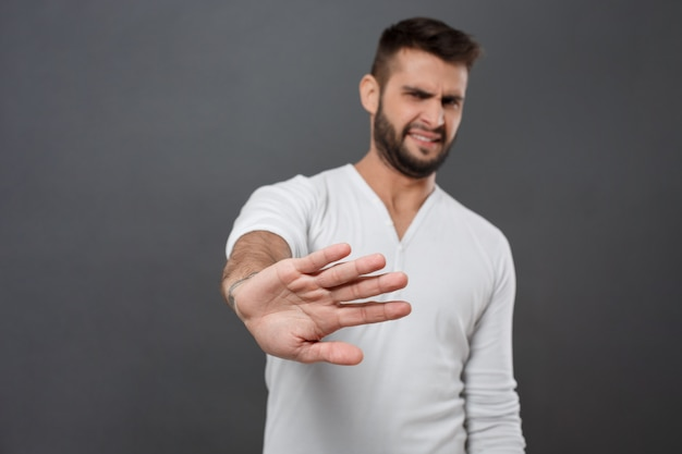 Displeased man refusing, stretching hand  over grey wall