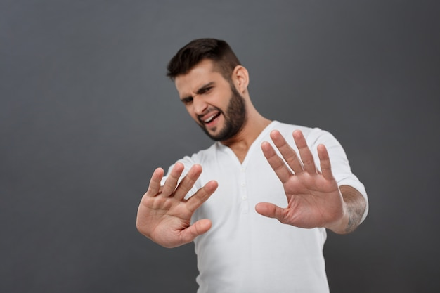 Displeased man refusing, stretching hands  over grey wall