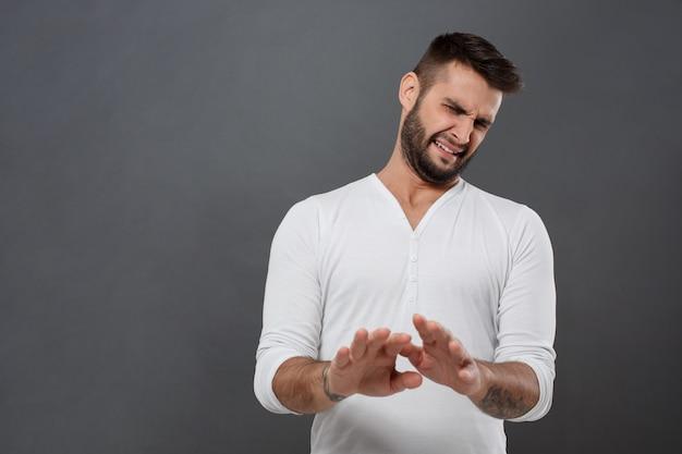 Недовольный мужчина отказывается, протягивая руки над серой стеной