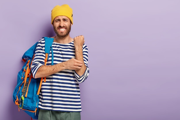 Displeased man scratches itch hand, suffers from dermatology problem, dressed in casual clothes, has travel with tourist backpack, clenches teeth, isolated over purple background, copy space area