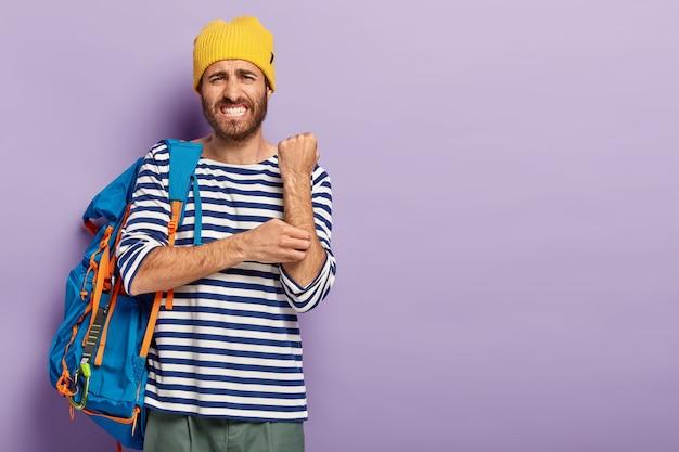 不機嫌な男はかゆみの手を引っ掻く、皮膚科の問題に苦しんでいる、カジュアルな服を着て、観光客のバックパックを持って旅行している、歯を食いしばっている、紫色の背景で隔離、コピースペースエリア