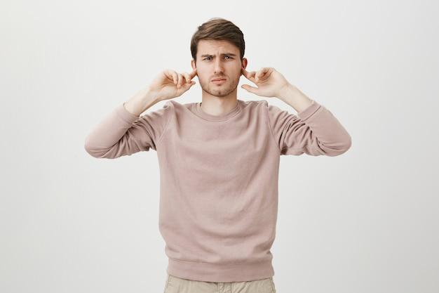 Displeased man shut ears from loud noise