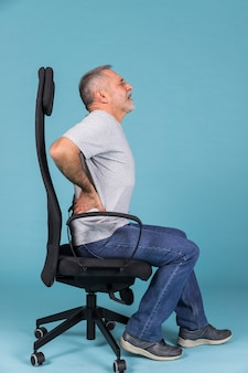 Displeased man sitting in chair having backache on blue backdrop