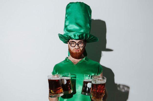 Displeased man in st.patriks costume holding many cups