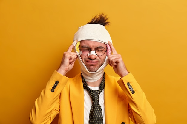 Displeased man suffers from unbearable migraine after injury, dressed in formal clothes, has bruises and broken nose, recovers after difficult surgery operation, isolated on yellow wall