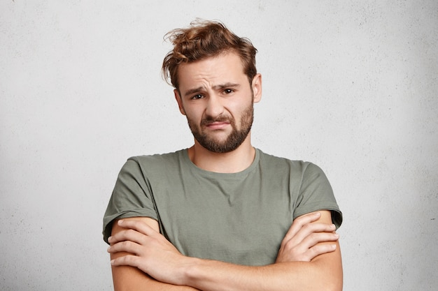 L'uomo dispiaciuto con barba e baffi aggrotta le sopracciglia, esprime esitazione e preoccupazione,