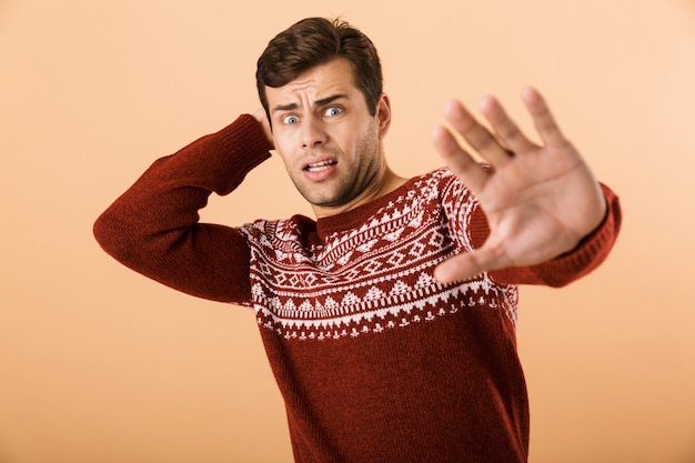 Displeased man with stubble wearing knitted sweater doing stop gesture with hands, isolated over beige wall