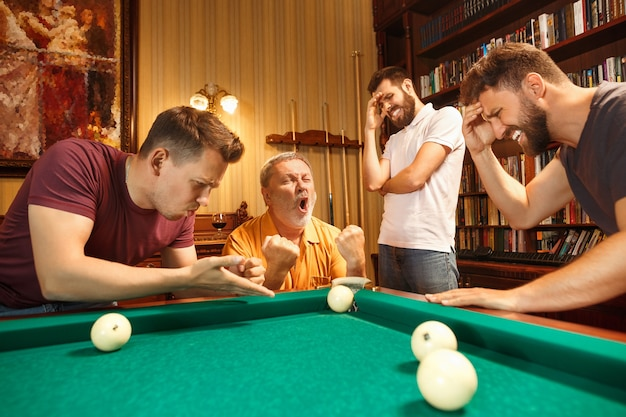 The displeased men playing billiards at office or home after work.