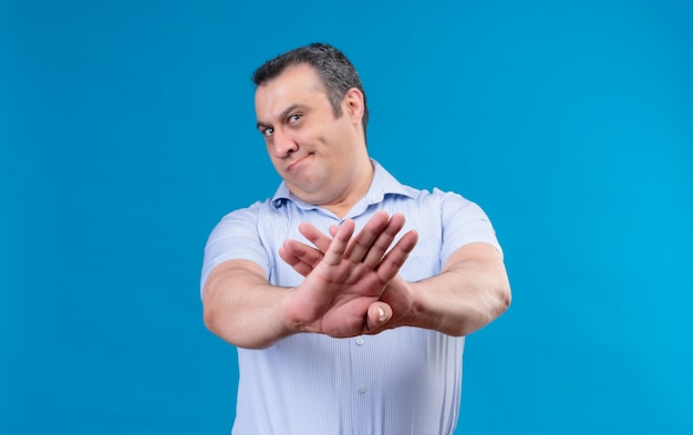 Displeased middle age man in blue vertical striped shirt raising hands in rejection on a blue space