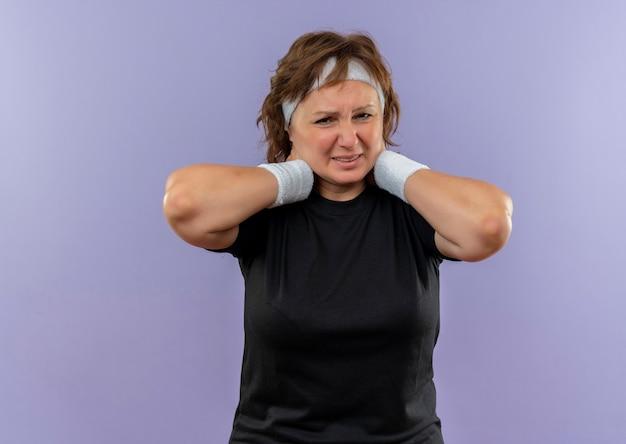 Donna sportiva di mezza età dispiaciuta in maglietta nera con archetto alla ricerca di malessere toccando il collo sensazione di dolore in piedi sopra la parete blu