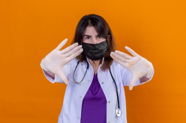 Medico donna di mezza età dispiaciuto che indossa camice bianco nella maschera facciale protettiva nera e con lo stetoscopio in piedi con le mani aperte facendo il segnale di stop con espressione seria e fiduciosa difende