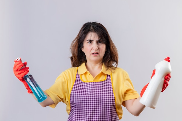 Displeased middle aged woman wearing apron and rubber gloves holding cleaning supplies