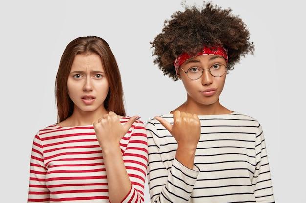 不機嫌な混血の女性の友人は論争を起こし、お互いを指さし、肩を並べて立ち、喧嘩の後に不満を感じ、縞模様のセーターを着て、白い壁に隔離されました