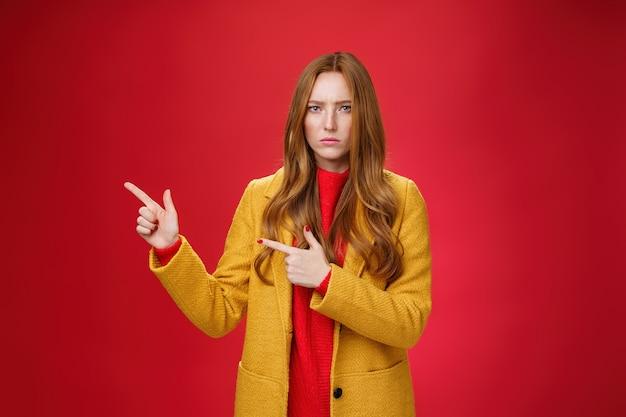 不機嫌で憂鬱なガールフレンドが質問をし、左上隅を指差して侮辱から顔をしかめ、失望し、赤い背景に不満を持って動揺した。