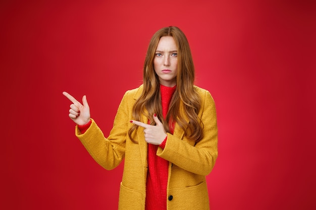 Displeased offended and gloomy girlfriend asking question, pouting and frowning from insult pointing at upper left corner disappointed and upset posing dissatisfied against red background.