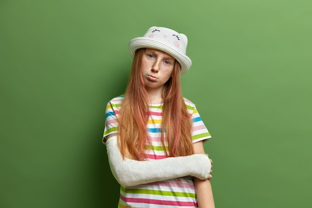 Displeased offended redhead girl with freckled face, being in bad mood after getting trauma, tilts head and purses lips, wears hat and striped t shirt, poses against green wall.