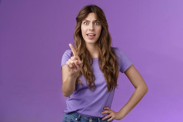 不機嫌な気分を害した真面目な断定的な女性は、明白な嫌悪感を禁じ、不承認の眉をひそめ、イライラする人差し指を振るのを禁止します。