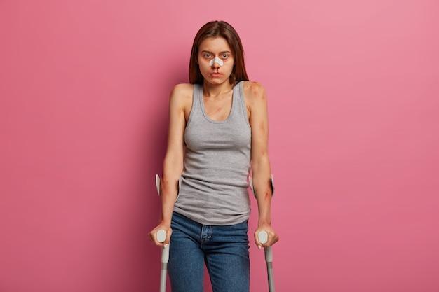 不機嫌な貧しい若い女性は、休日の事故後に身体的損傷を持っています