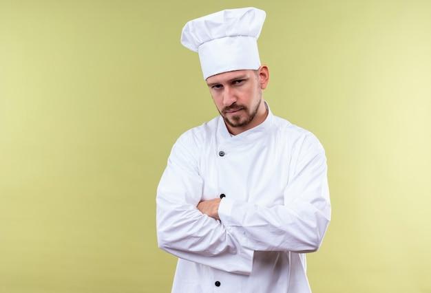 白い制服を着た不機嫌なプロの男性シェフが腕を組んで緑の背景に自信を持って見て立っている帽子を調理