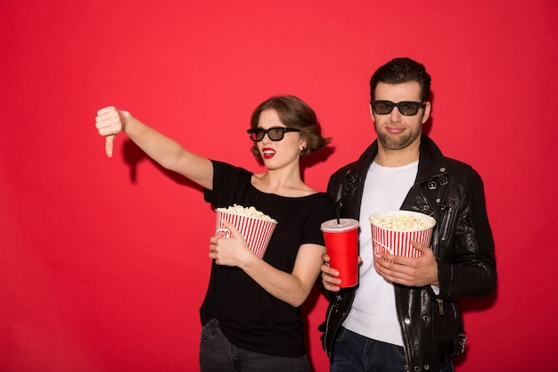 Displeased punk couple in eyeglasses with popcorn and soda