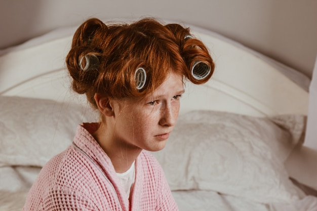 Displeased red-haired girl holds her arms crossed near the face. she looks with a sullen expression, being unhappy as she was curled on hair curlers. does not want to have a curly hairstyle, posing.