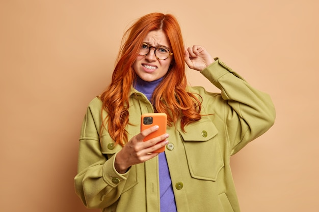 Displeased red haired woman scratches head frowns from dissatisfaction tries to solve problem with smart phone doesnt know how to use new application dressed in fashion clothes.